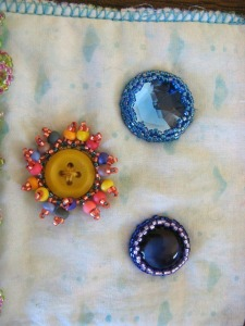 Two cabochons, plus a button flower.