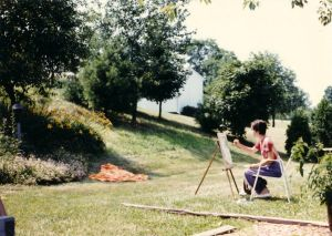 One of the few pictures I have that shows a bit of the yard. My sister Cleo painting in 1987. Notice all the TREES.