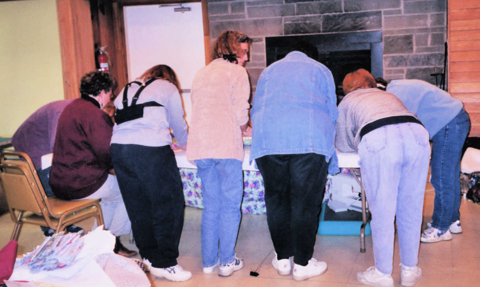 The back of a group of quilters removing borders from a quilt in progress.