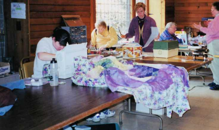 Quilting retreat; woman sewing on a quilt with others in the background working and talking.