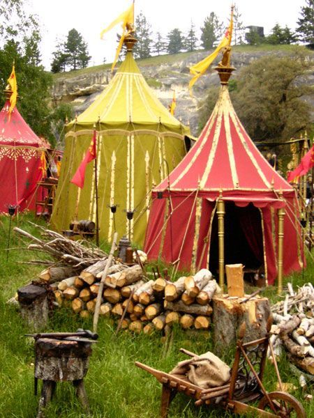 Medieval campground colorful tents and rustic tools.